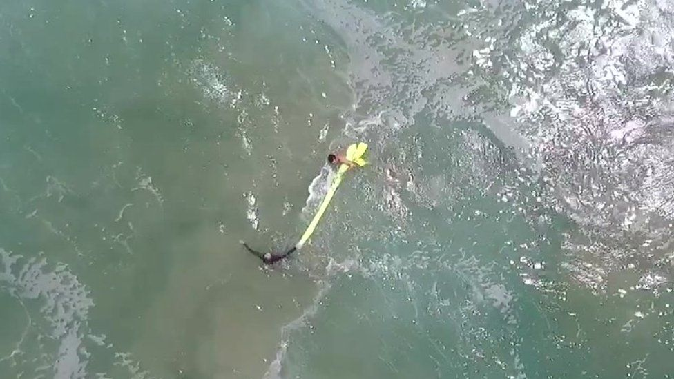 A screengrab shows the two boys clinging to the yellow inflatable as they swim back to shore