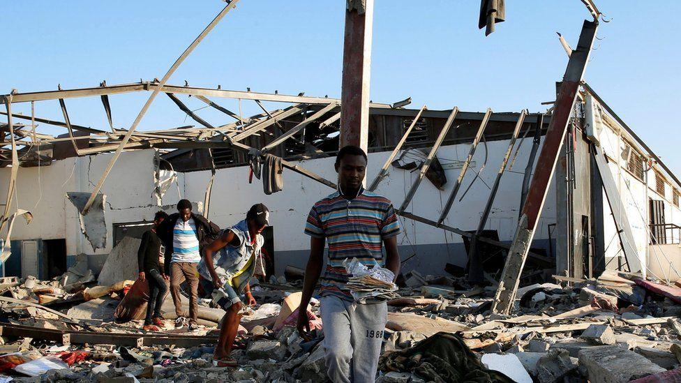 مهاجرون يحملون بقايا ممتلكاتهم من بين الأنقاض في مركز احتجاز للمهاجرين الأفارقة الذين تعرض لضربة جوية في ضاحية تاجوراء بالعاصمة الليبية طرابلس 3 يوليو / تموز الماضي