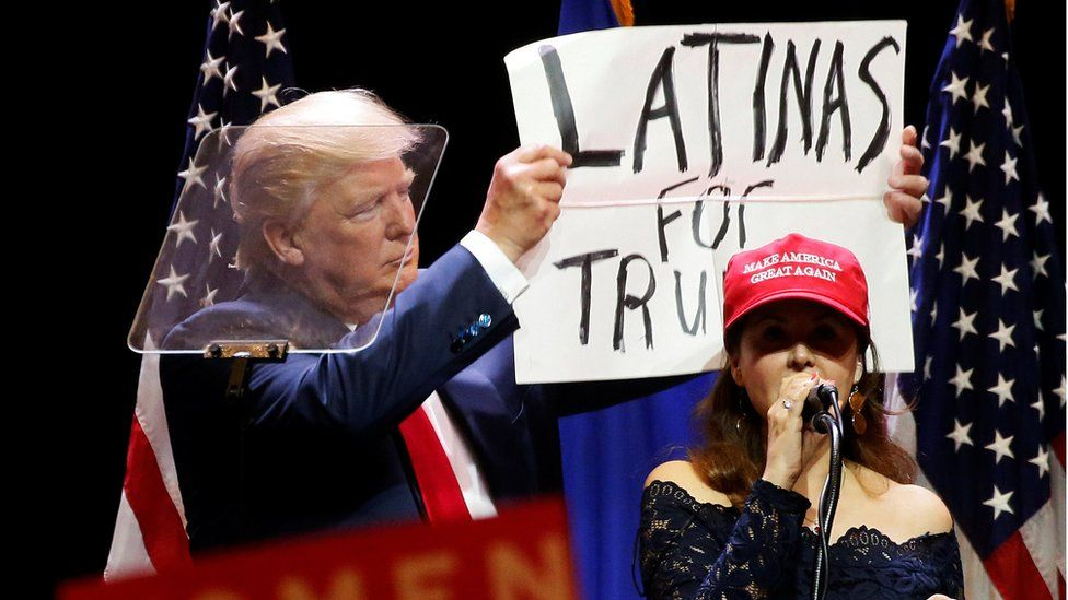 "A woman joins Republican presidential nominee Donald Trump as he holds up a ""Latinas for Trump"" sign during a campaign rally at the Venetian Hotel in Las Vegas, Nevada, U.S. October 30, 2016"