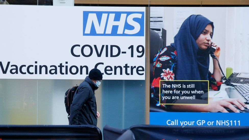 Man walks past NHS Covid-19 Vaccination centre poster