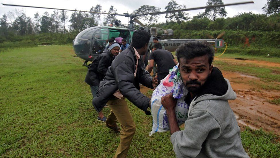 People unloading goods from an army helicopter