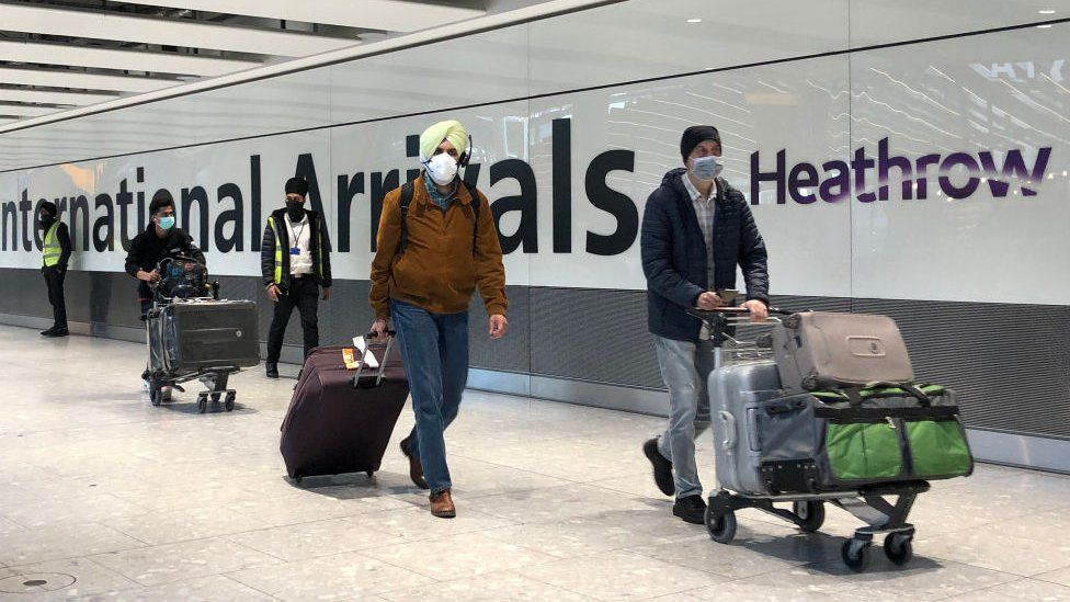 Passengers are escorted through the arrivals area of terminal 5 towards coaches destined for quarantine hotels, after landing at Heathrow airport