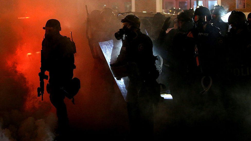 Police stand amongst tear gas in Ferguson, Missouri