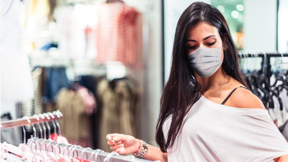 woman in clothes shop with mask