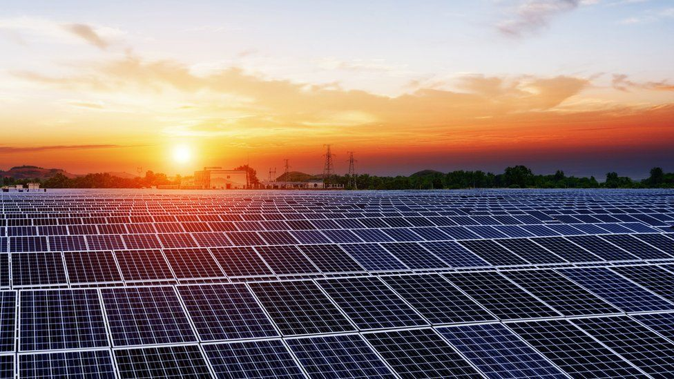 The Sun rises over rows over solar panels