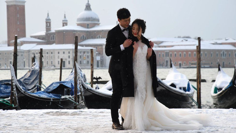 A couple poses in St. Mark's Square in Venice