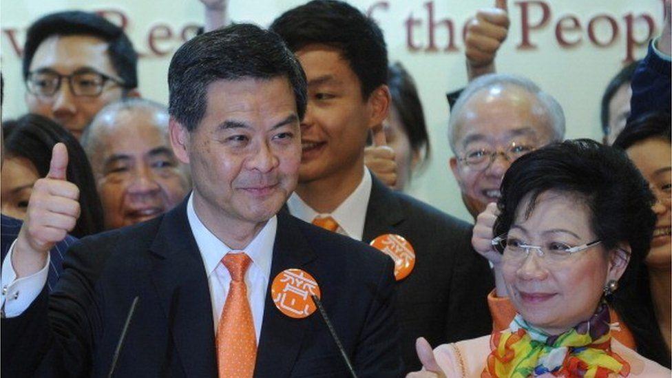 Hong Kong chief executive elect Leung Chun-ying (L) and his wife Regina Leung (R) gives a thumbs up sign at a press conference after Leung Chun-ying won the Hong Kong chief executive election on March 25, 2012