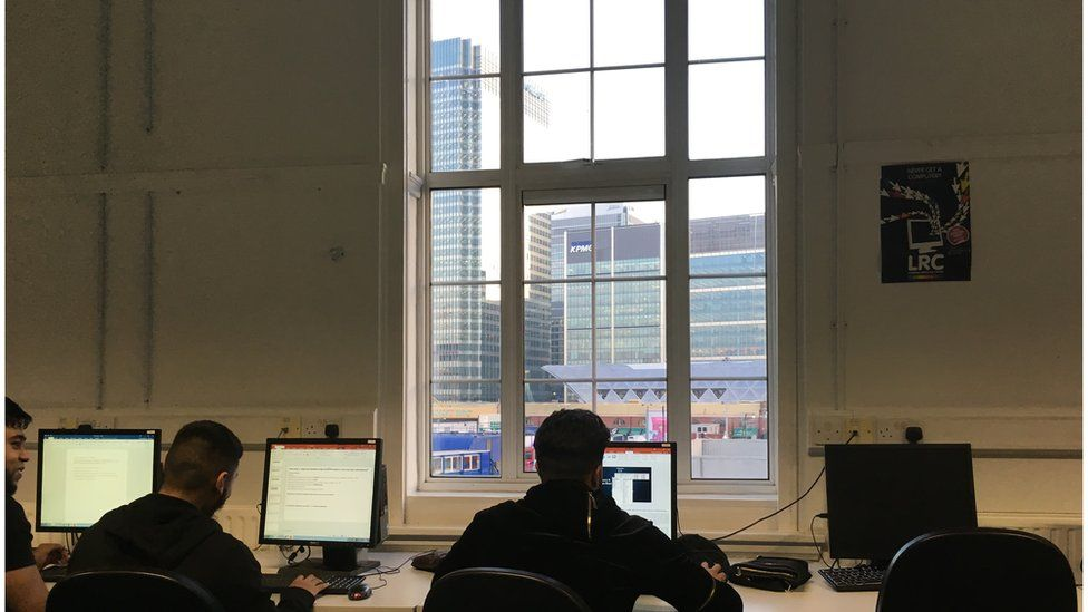 Pupils looking over of the window of Tower Hamlets College, where classrooms overlook Canary Wharf