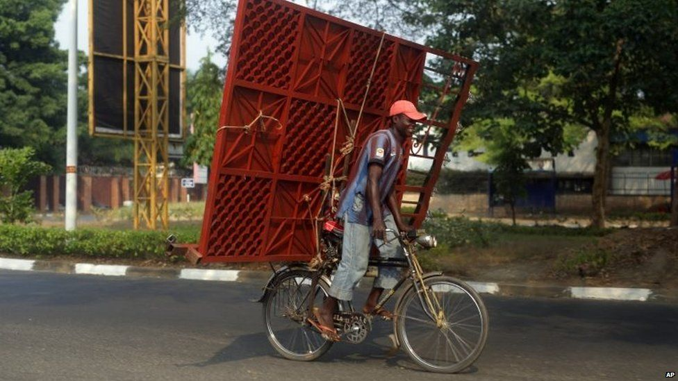A cyclist carries a metal gate on the back of his bicycle in Bujumbura, Burundi (July 2015)