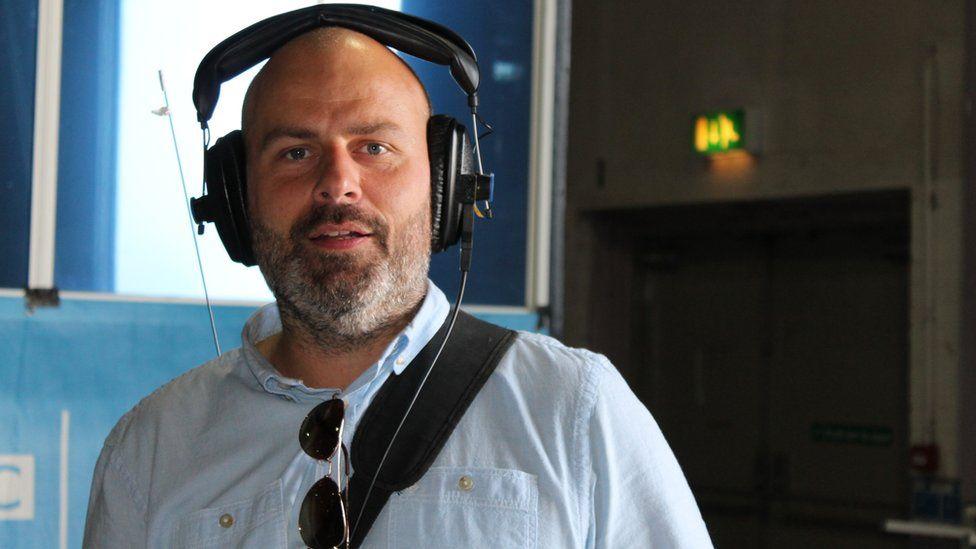 Mae Aled Hughes yn edrych ymlaen i gael asesu moch Môn ar ôl ei raglen ar BBC Radio Cymru