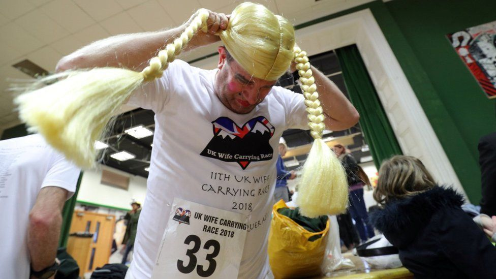 Malcolm Pernet puts on a wig as he prepares to carry Kate Barfield in the annual UK Wife Carrying Race
