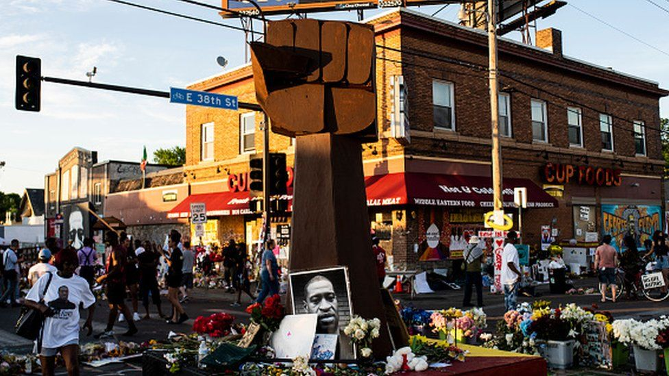 A sculpture of a raised fist stands in a memorial for George Floyd outside Cup Foods