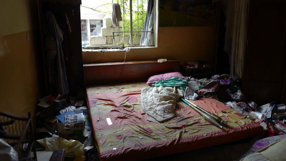 "A messy bedroom with rockets thrown across the bed before the window. Originally tweeted by @BowenBBC with the caption: ""Another bedroom on the front line in #Mosul, more privacy invaded. Clothes still in the wardrobe. RPGs on the bed."""