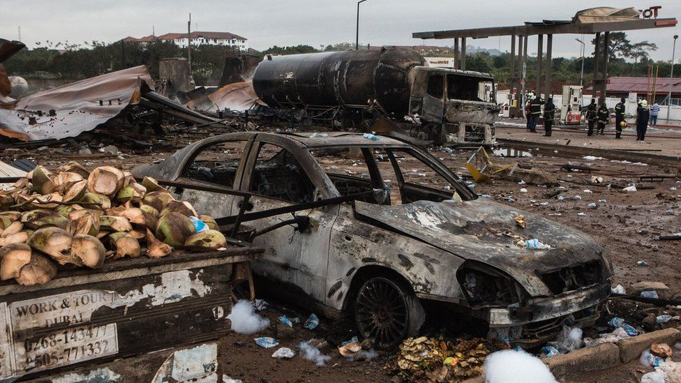 "A picture taken on October 8, 2017 in Accra shows burnt vehicles on the site where a gas tanker caught fire, triggering explosions at two fuel stations on the evening of October 7, 2017. At least three people were killed and dozens injured after a tanker truck carrying natural gas caught fire in Ghana""s capital, Accra, triggering explosions at two fuel stations, emergency services said on October 8, 2017. / A"