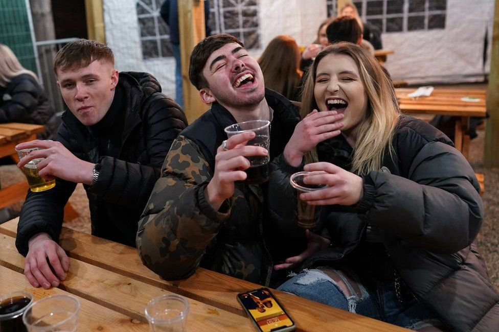 Drinkers laugh and whilst holding pints of beer