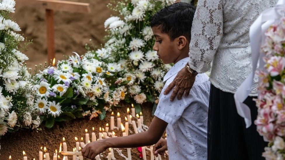 "A young boy lights a candle at a grave after a funeral for a person killed in the Easter Sunday attack on St Sebastian""s Church, on April 25, 2019 in Negombo, Sri Lanka."