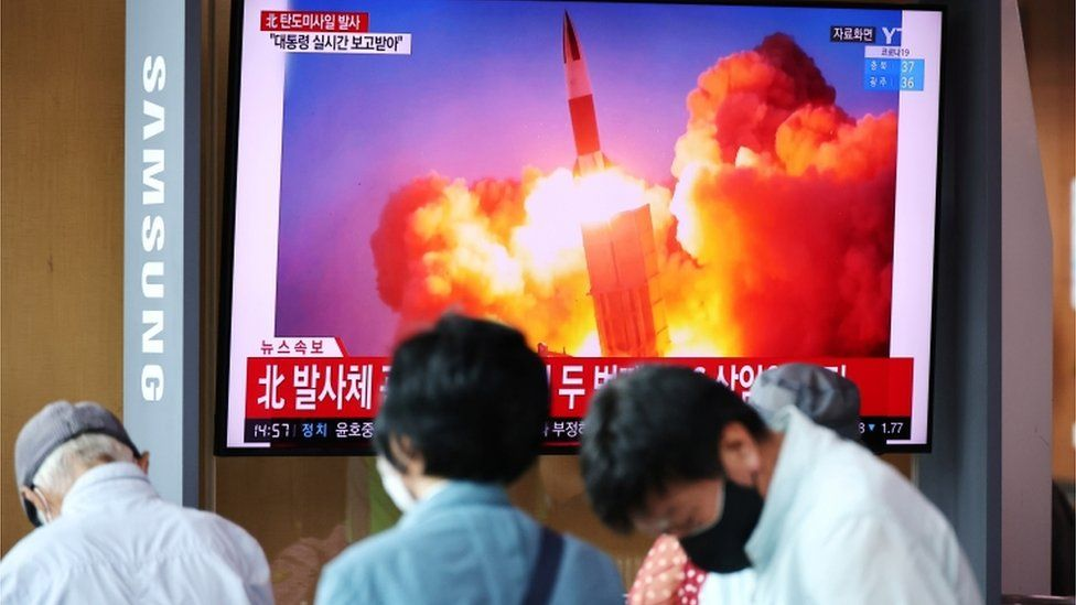 People watch a TV broadcasting file footage of a news report on North Korea firing what appeared to be a pair of ballistic missiles off its east coast, in Seoul