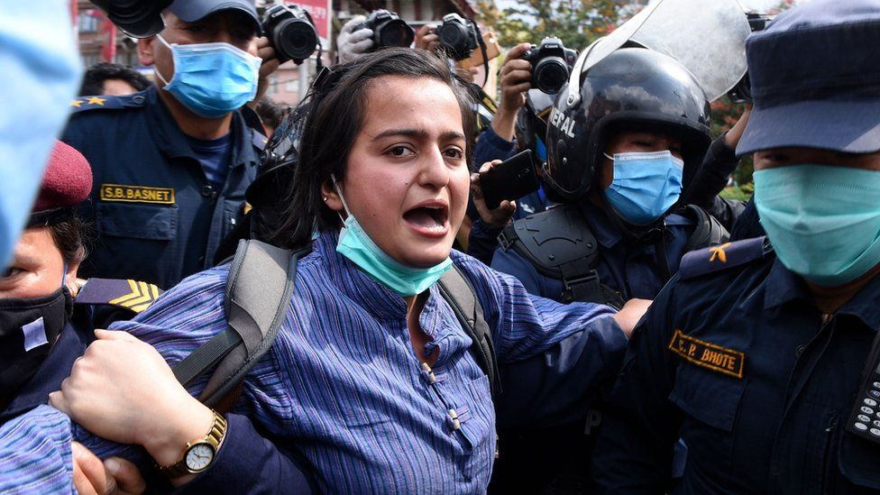 """A demonstrator shouts slogans as she is detained by police during a protest against India""""s newly inaugurated link road to the Chinese border, in Kathmandu on May 12, 2020."""