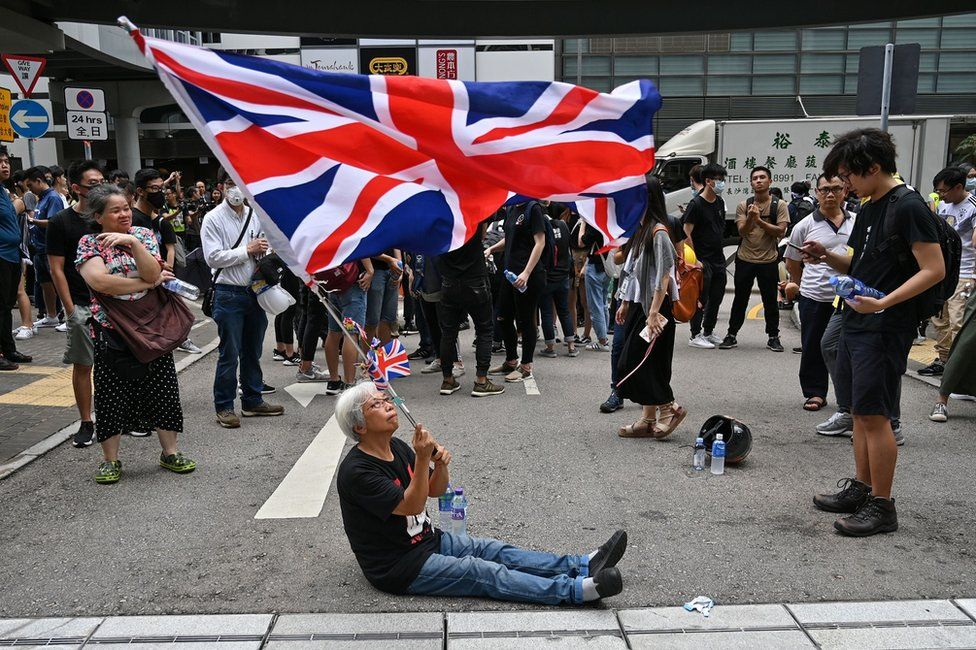 A woman waves a British Union Jack flag during a protest near the government headquarters in Hong Kong on June 21, 2019