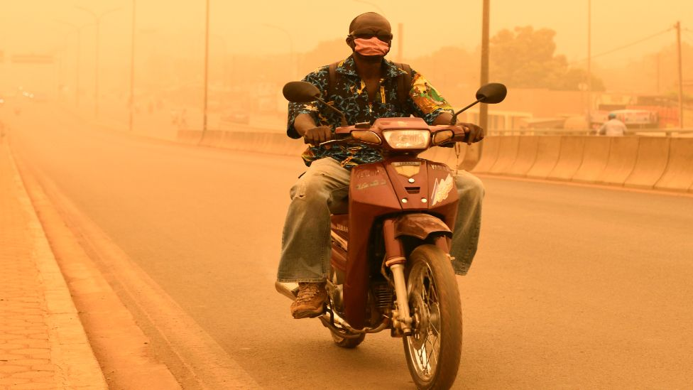 A man rides his motorcycle during a sandstorm