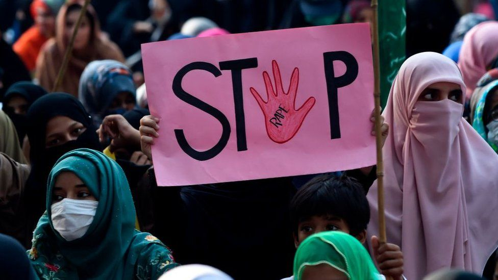 "A woman holds a placard reading ""Stop"" during a protest against an alleged gang rape of a woman in Pakistan, 2020"
