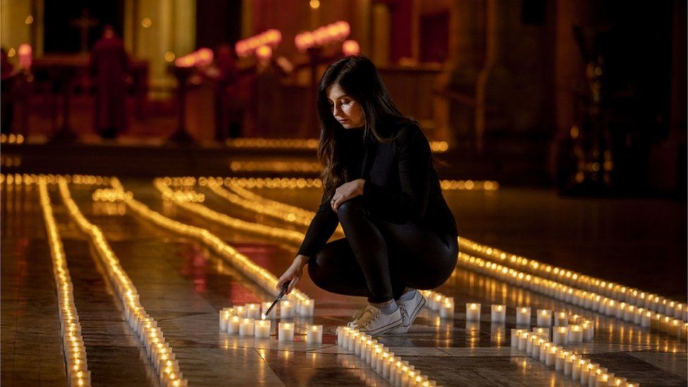 Holly Wilson, whose grandmother Ada Wilson passed away during the pandemic, lights a candle in Belfast Cathedral - the floor of the cathedral is covered in the lights