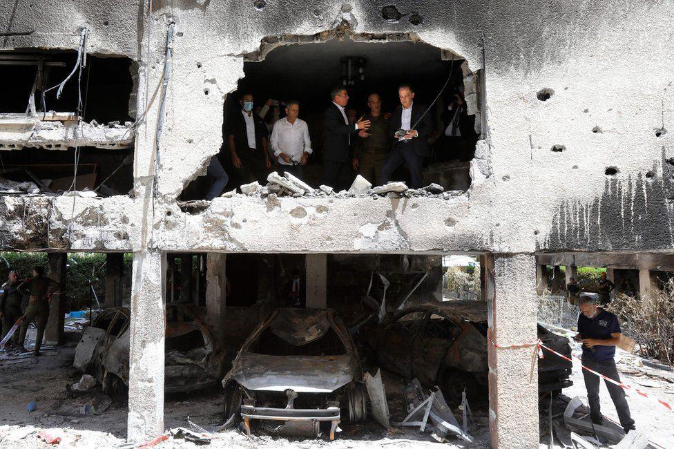 Israeli Foreign Minister Gabi Ashkenazi and his German counterpart Heiko Maas stand in a heavily damaged building in Petah Tikva, Israel