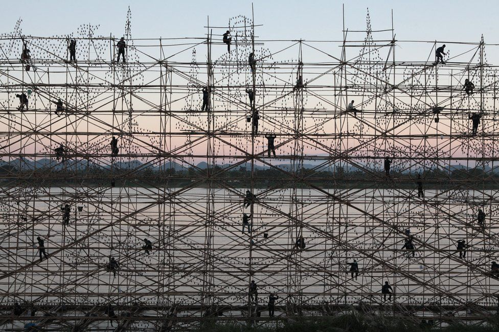 Men stand on scaffolding stand against a setting sun
