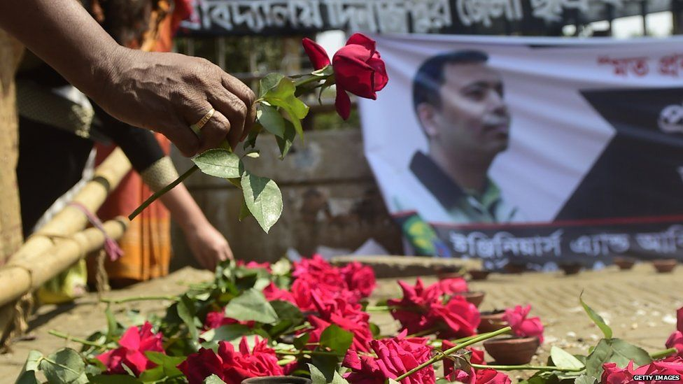 A mourner carries a rose in honour of Avijit Roy