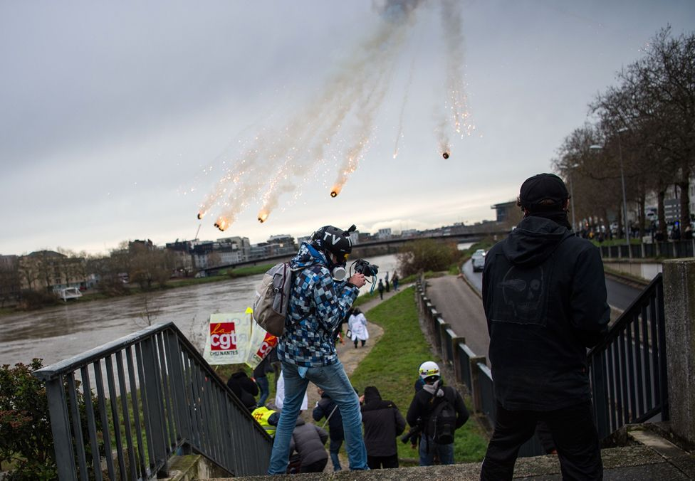 People take cover as riot police fire tear gas canisters