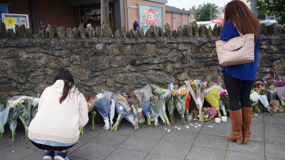 People leave flowers in the Keyham area of Plymouth after five people died in a shooting on 12 August 2021