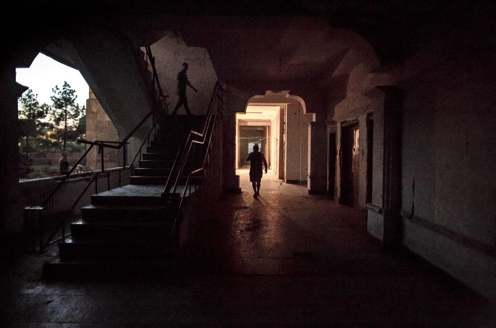 Residents walk through the first floor hallway at dusk