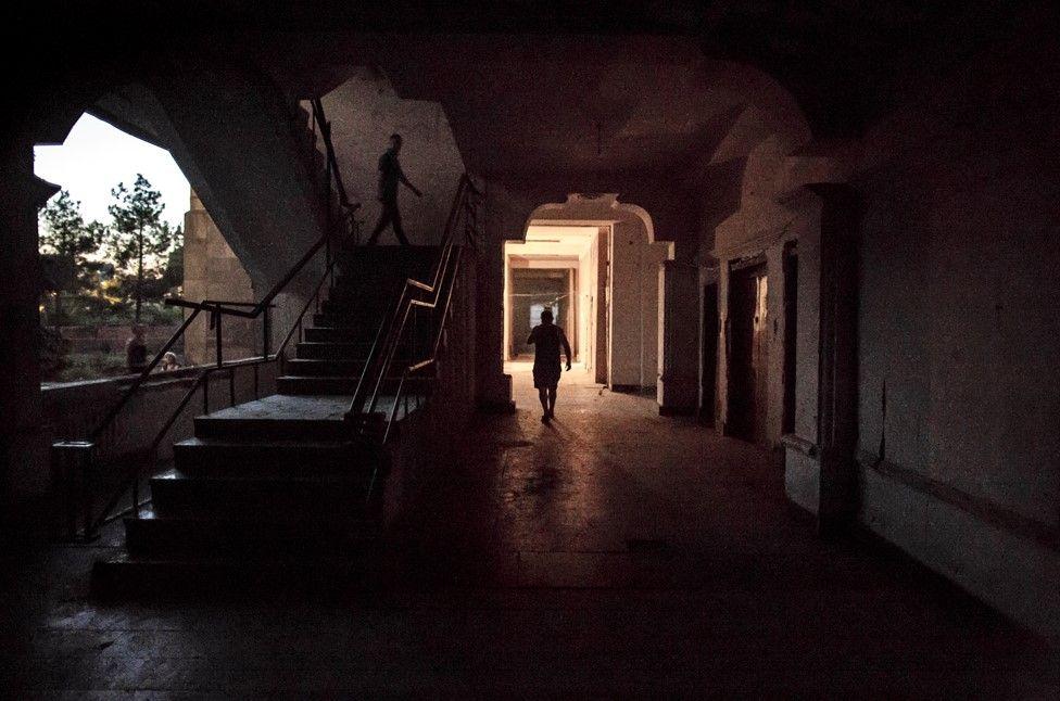 Residents walk through the first floor hallway at dusk