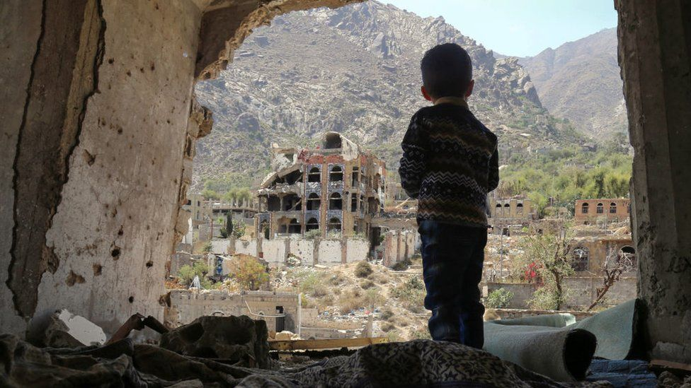 A Yemeni child looking out at buildings that were damaged in an air strike in the southern Yemeni city of Taez.