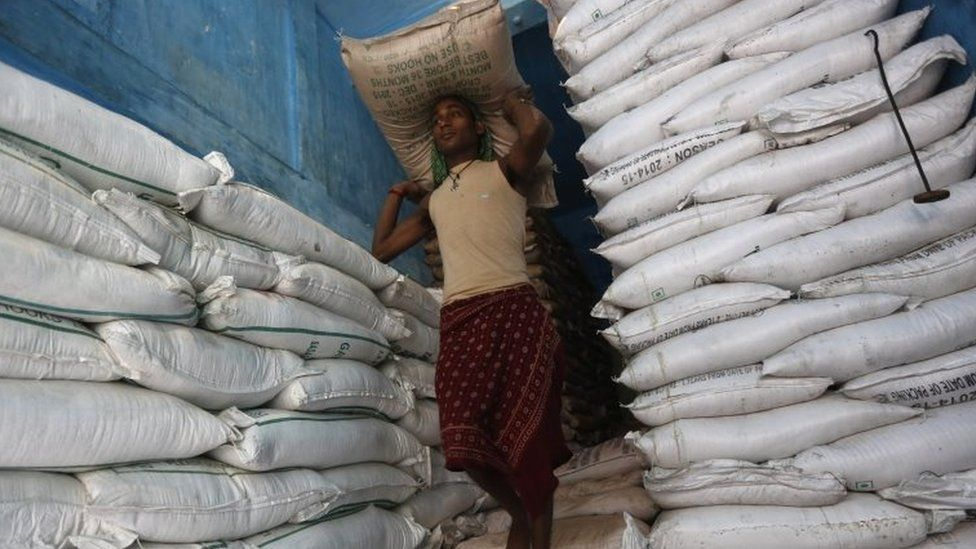 A labourer carries a sack filled with sugar in a store at a wholesale market in Kolkata, India, February 15, 2016