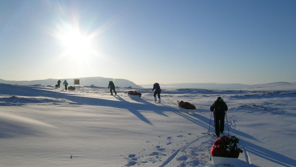 A line of Arctic explorers walk on into the icy wilderness