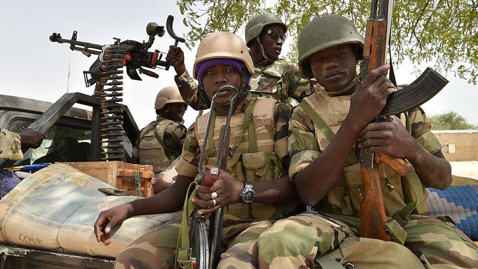 Soldiers sit aboard a military vehicle at Bosso military camp on June 17, 2016 following attacks by Boko Haram fighters in the region