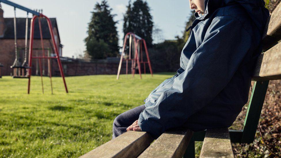 Sad child on a bench