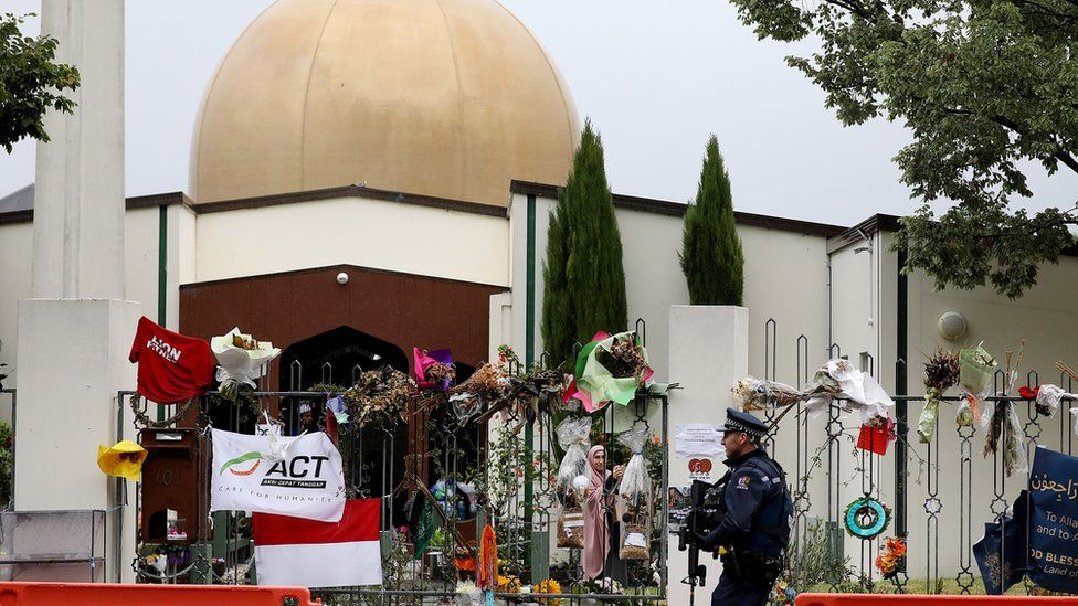 An armed police officer stands guard outside the Al Noor mosque in Christchurch where dozens were killed in March