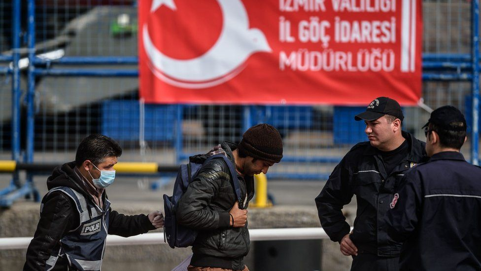 This file photo taken on April 8, 2016 shows a police officer escorting a migrant from a Turkish ferry carrying the second group of migrants deported from Europe to Turkey as they arrive at the port of Dikili district in Izmir. Turkey on March 15, 2017