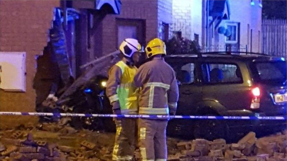 Fire service at scene where car has driven through corner of house in west Belfast