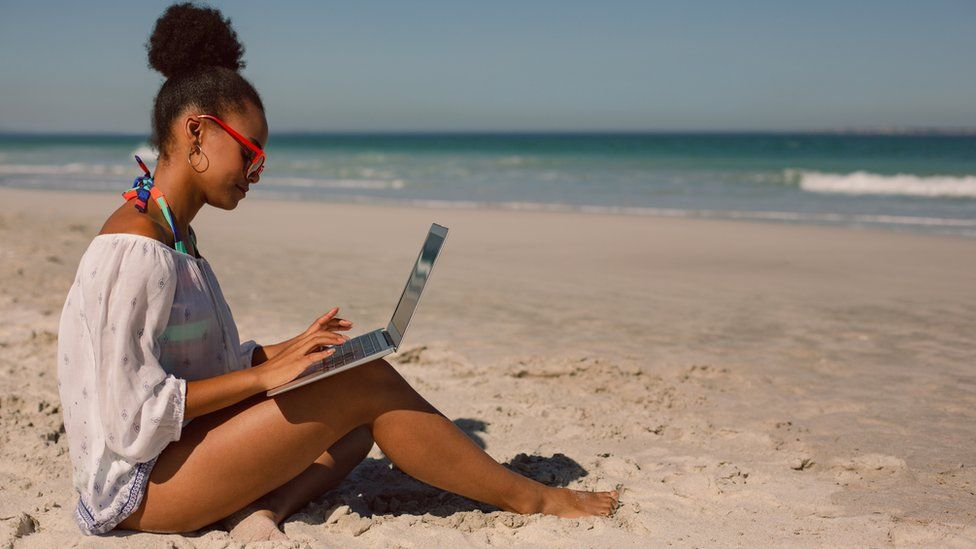 A woman on the beach with a laptop