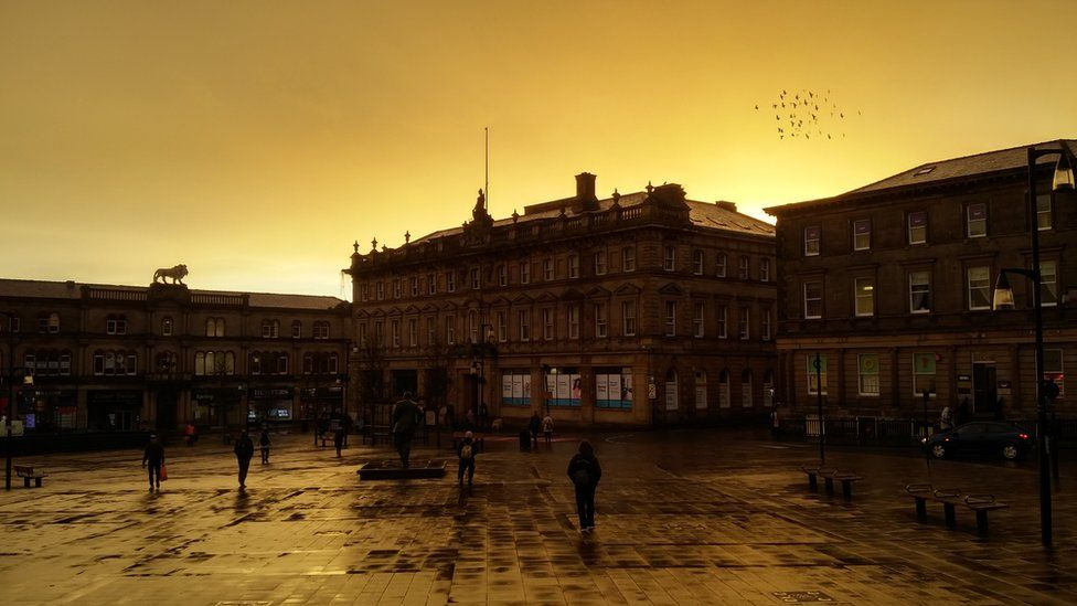 A photo of the square with a yellowy sky