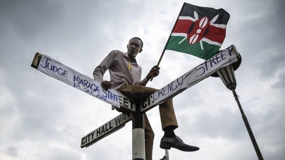 """A supporter of The National Super Alliance (Nasa) opposition coalition and its presidential candidate Raila Odinga sits on top of a street sign post that has been relabeled """"Judge Maraga Street"""", referring to Chief Justice David Maraga,"""