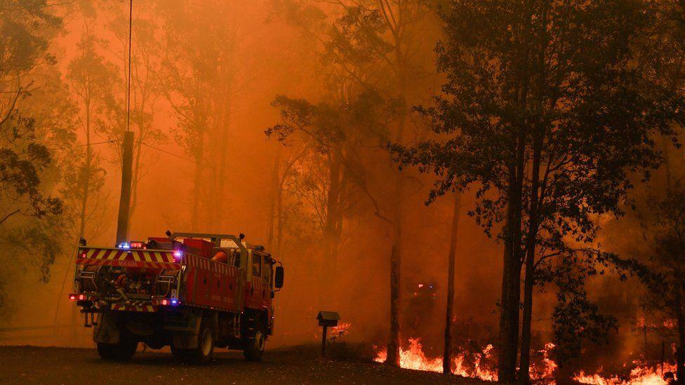 A fire truck near a raging fire in Werombi, south-west of Sydney, against a bright orange sky
