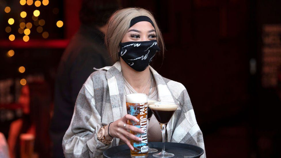A woman wearing a face mask carries a tray of drinks at Pitch bar on April 30, 2021 in Cardiff, Wales.