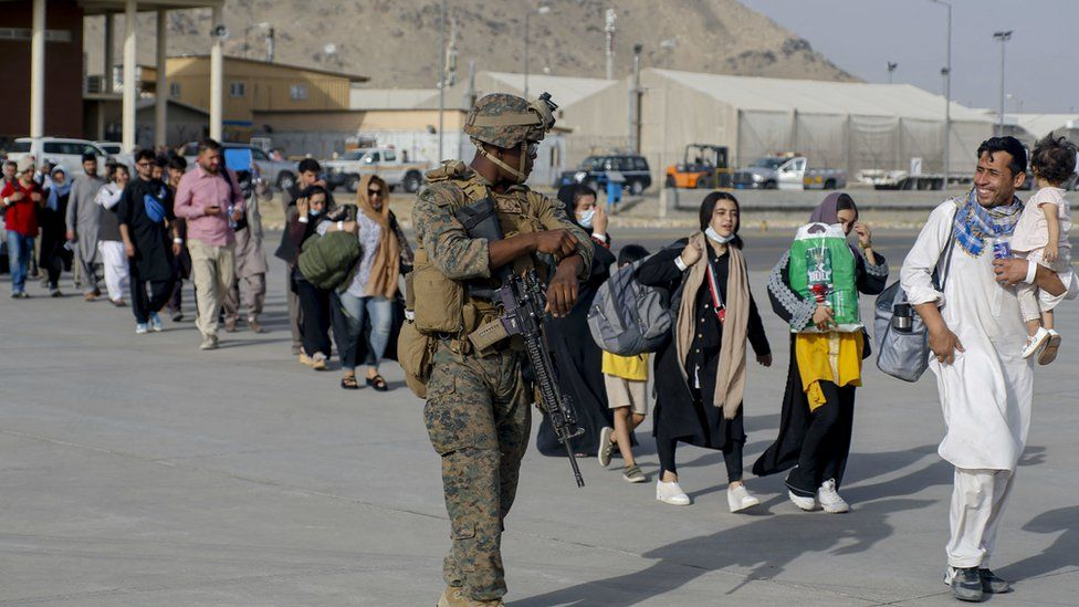United States Marines assigned to 24th Marine Expeditionary Unit escorts evacuees during an evacuation at Hamid Karzai International Airport, Afghanistan