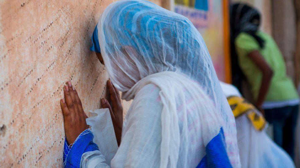 Asmara, people praying in a church