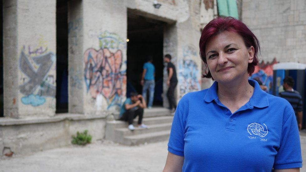 Amira, in a blue and white collared t-shirt, stands in front of graffiti-marked pillars between which men loiter