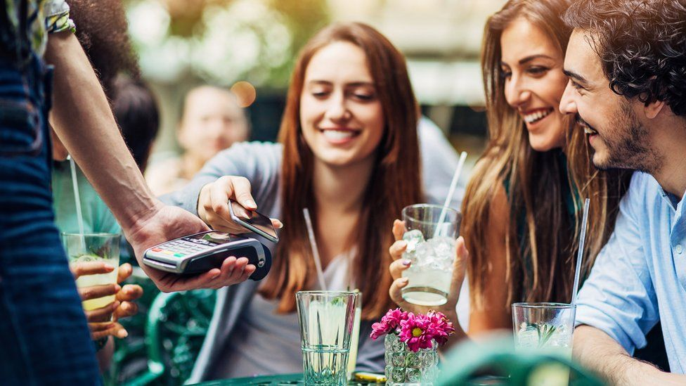 A woman uses her smartphone to pay for a meal at a restaurant with friends